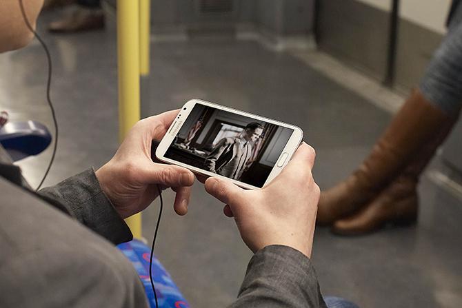 usuário de smartphone com tv digital no ônibus