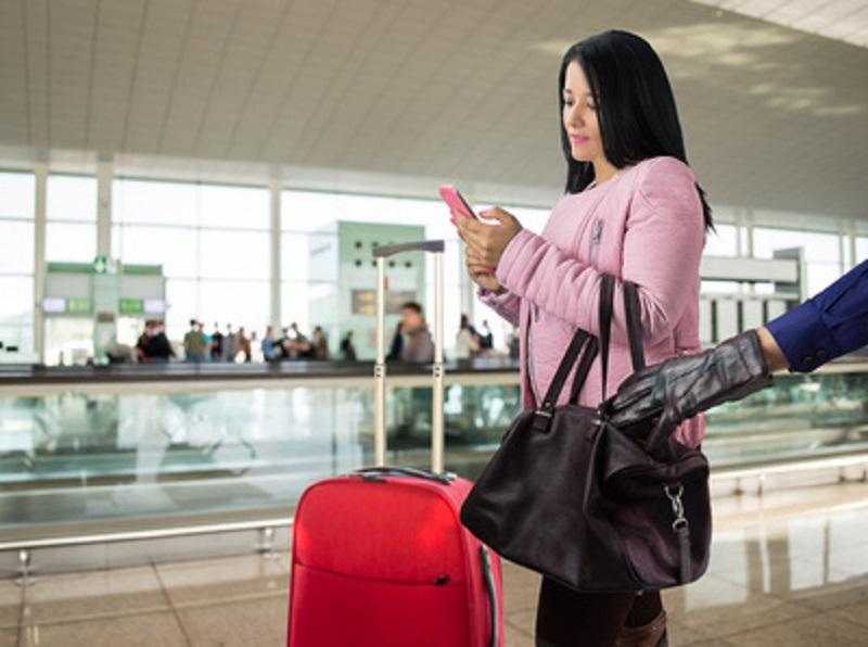Mulher distraída tendo seu celular roubado