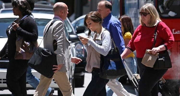 Pessoas na rua com o celular na mão