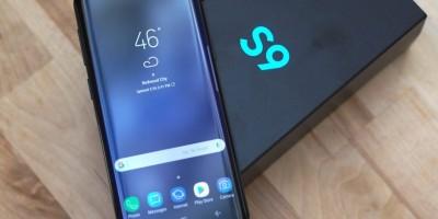 """Galaxy S9 preto com a tela acionada, apoiado na caixa do aparelho, preta e com a inscrição """"S9"""" em azul turquesa. Ambos estão dispostos sobre uma mesa de madeira."""
