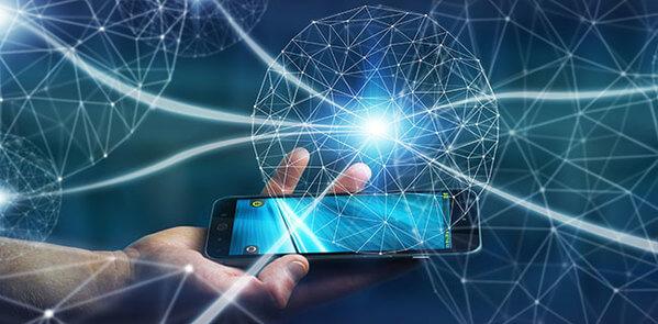 Mão segurando um celular com o desenho de um globo sobre ela, em linhas azuis, simbolizando o desenvolvimento tecnológico.