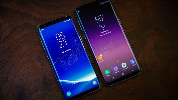Galaxy S9 e Galaxy S9 Plus, um ao lado do outro. Ambos estão com as telas ligadas, dispostos sobre uma mesa de madeira.