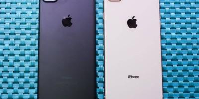 Foto de 2 iPhones 8 Plus com a parte traseira para cima, dispostos em uma superfície de fibra entrelaçada na cor azul. O aparelho da esquerda é da cor cinza-espacial, enquanto o da direita é prateado.