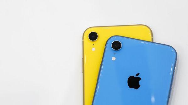 Dois aparelhos iPhone XR com sua parte traseira em destaque. O da frente é azul e o de trás é amarelo, e ambos estão sobre uma superfície branca.