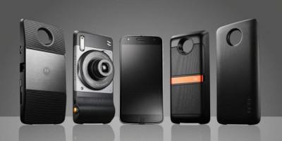 Snaps do Moto Z 1ª geração, com projetor, câmera, falante da JBL e power pack. No meio, aparece o Moto Z 1ª geração, na cor preta. O fundo da imagem é cinza em gradiente.