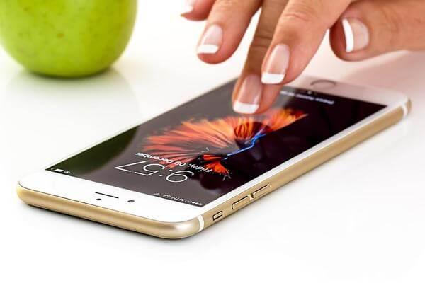 Mulher mexendo em um iPhone dourado, que está sobre a mesa, com uma maçã verde ao fundo. O papel de parede do celular é de fogos de artifício.