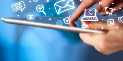 Pessoa segurando um celular e tocando em sua tela, com ícones de mensagens, contatos, busca e outros saltando da tela, simbolizando a transformação digital.