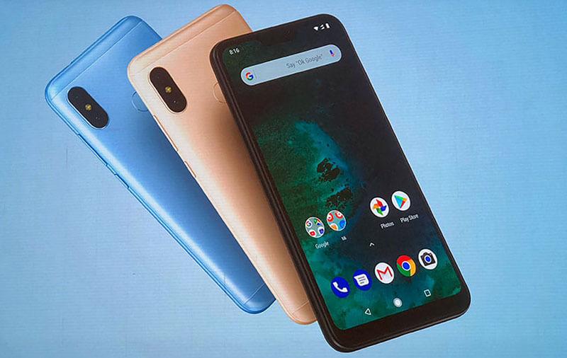 Foto com 3 aparelhos Xiaomi Mi A2 Lite sobre um fundo azul. O aparelho que aparece em maior destaque está de frente, tem a cor preta e está com a tela ligada, enquanto os outros dois estão dispostos com a parte traseira para cima, atrás do primeiro aparelho, nas cores rose gold e azul, respectivamente.