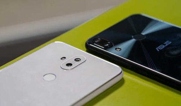 Zenfone 5 em duas cores, preto e branco. Ambos estão com a parte traseira para cima, sobre uma mesa verde.