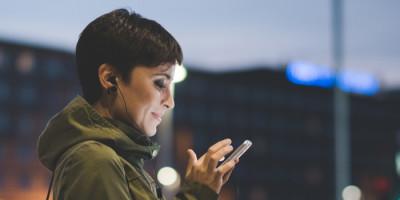 Jovem mulher utilizando o celular em rua movimentada