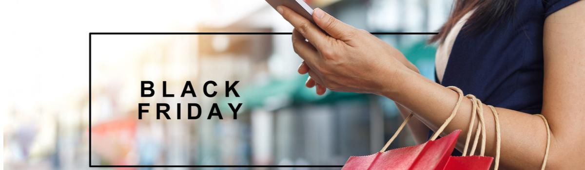Mão segura um celular e algumas sacolas, sobre fundo desfocado de uma rua, ao lado das palavras Black Friday