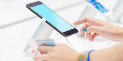 Como se preparar para a Black Friday: Mão testando aparelho de celular em uma loja.