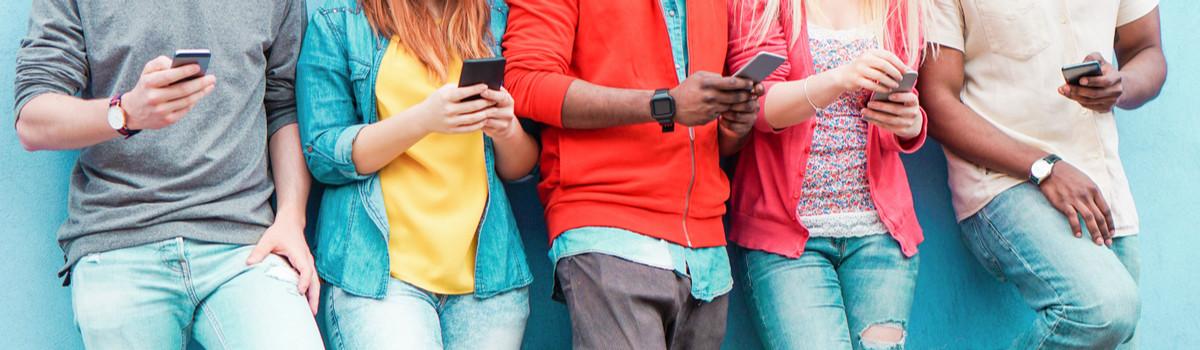Foto de jovens encostados em uma parede azul. Cada um deles segura um celular nas mãos.