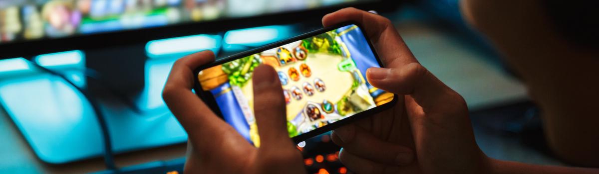 Mãos segurando um smartphone gamer, com o visor mostrando o jogo.