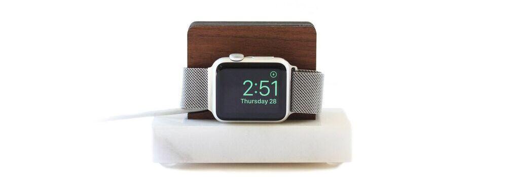 Smartwatch sobre uma base de madeira com fundo branco.