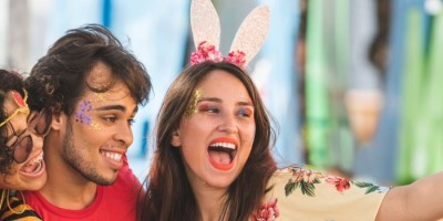 Cuidados no carnaval 2020: Duas mulheres e um homem, fantasiados para o carnaval, tirando selfie em uma rua.