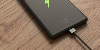 Primeira carga do celular: Smartphone ligado ao carregador sobre uma superfície de madeira.
